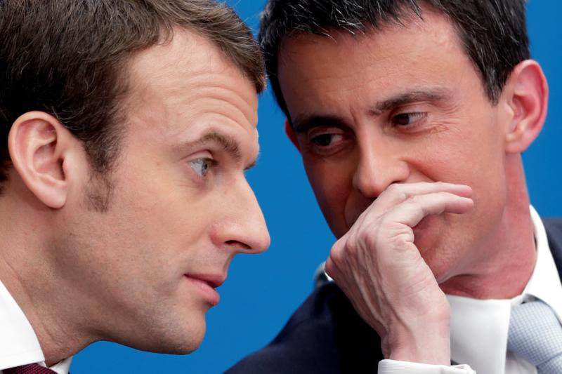 FILE PHOTO French Prime Minister Manuel Valls (R) speaks with then Economy minister Emmanuel Macron at the Elysee Palace in Paris, April 8, 2015. Former French Socialist prime minister Manuel Valls said May 9, 2017 that he wanted to stand for President-elect Emmanuel Macron's political movement in June parliamentary elections, the first high-profile defection since Macron's election win. Picture taken April 8, 2015. REUTERS/Philippe Wojazer/File Photo