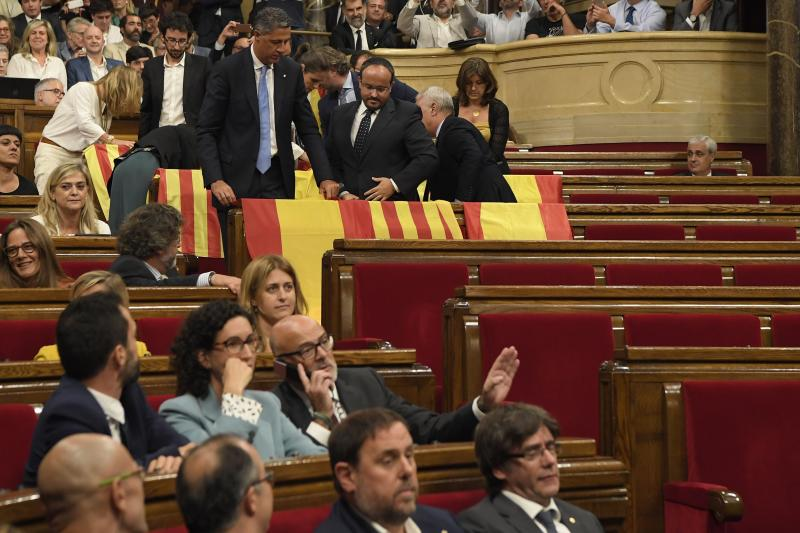 Deputies of the Partido Popular (PP) display Spanish flags as they leave the Catalan Parliament before the vote on a bill for a referendum on independence in Barcelona, on September 6, 2017. Catalonia's parliament passed a law on September 6, 2017 paving the way for an independence referendum on October 1 which is fiercely opposed by Madrid, setting a course for Spain's deepest political crises in decades. The law was adopted with 72 votes in favour and 11 abstentions. Lawmakers who oppose independence for the wealthy northeastern region of Spain abandoned the chamber before the vote. / AFP PHOTO / LLUIS GENE