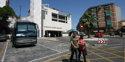 Turistas, en primer término, un autobús y, al fondo, el parking de Galarza y la torre-ascensor, que se pintará. | Lorenzo Cordero