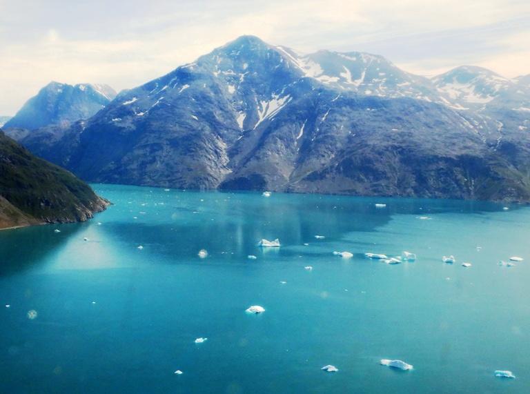 ¡Estamos llegando! El Boeing 737 ha dado una vuelta en redondo para perder altura y velocidad, ha desplegado los flaps y bajado el tren de aterrizaje. Ante nosotros el Iserfillialik de 1752 metros de altura, quizá una de las montañas más altas de fiordo. Antaño fue utilizada para avisar mediante grandes fuegos en su cima, de la presencia de barcos y también fue la tumba de los grandes señores Vikingos. En el agua el cinturón de bloques de hielo de 15 a 20 de altura del glaciar Qooqqut. ¡Estamos en casa de nuevo! 