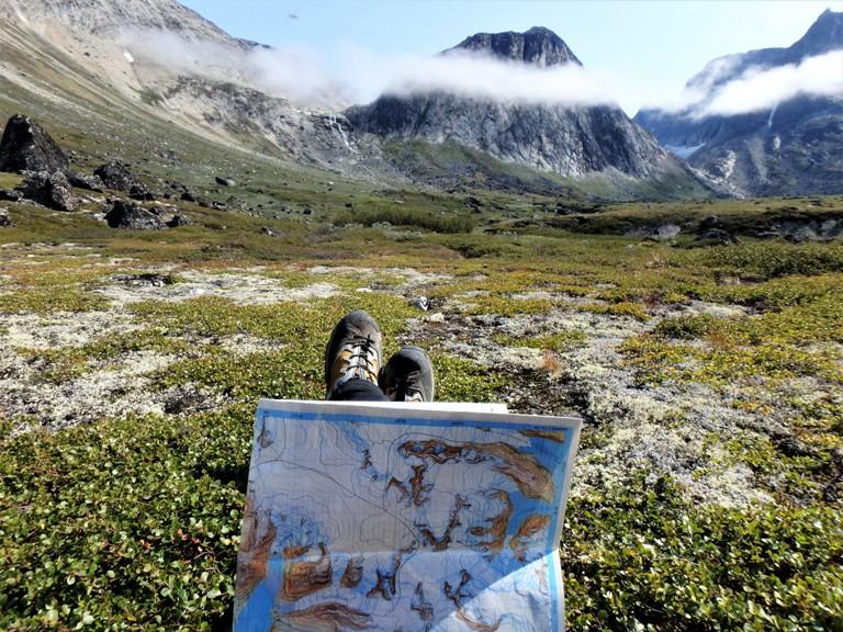 """Parada para estudiar el mapa, nos encontramos la primera dificultad, el paso """"fácil"""" al glaciar atraviesa un nevero y una fuerte pendiente de tierra suelta encima de un acantilado de un par de cientos de metros."""